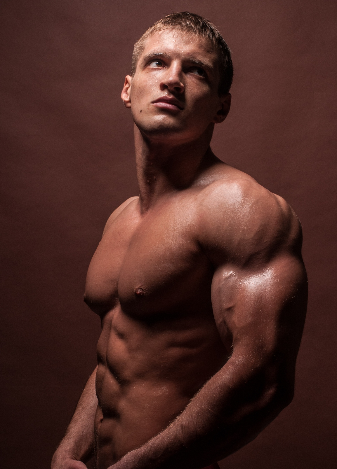 Young muscled male model posing shirtless in studio